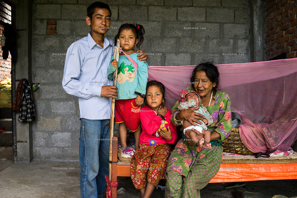 (L-R) Ratna Baniya (28), Aastha Baniya (6), Monika Baniya (7) and Bhagawati Baniya (56) cradling Sapana (2 months) pose for a family portrait in their temporary home in Chautara, Sindhupalchowk, Nepal on 29 June 2015. The three girls lost their mother during the April 25th earthquake that completely levelled their house. Aastha was buried under the rubble together with her mother but Aastha survived. As their father Ratna Baniya (28) cannot care for the children on his own, SOS Childrens Villages has since been supporting the grandmother with financial and social support so that she can manage to raise the children comfortably and ensure that they will all be schooled. Photo by Suzanne Lee for SOS Children's Villages