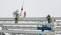 "Ethan Chalke and Jim Johnson of American Steele set the final beam with signatures of the people who have had a significant role in the project during the traditional ""Topping Off"" ceremony at the Gilford Marine Patrol building on Monday morning.  (Karen Bobotas/for the Laconia Daily Sun)"