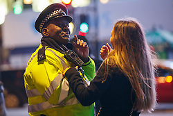 © Licensed to London News Pictures. 01/01/2017. London, UK. A police officer and a revellers chat as revellers celebrate the New Year in central London during the first hours of 2017 on January 1. Photo credit: Tolga Akmen/LNP