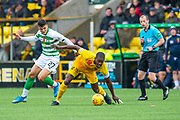 Marvin Bartley (#6) of Livingston FC holds off Mohamed Elyounoussi (#27) of Celtic FC, as referee Willie Collum watches on during the Ladbrokes Scottish Premiership match between Livingston FC and Celtic FC at The Tony Macaroni Arena, Livingston, Scotland on 6 October 2019.