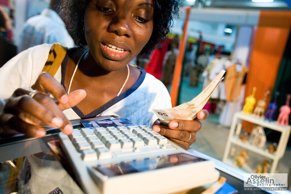 A vendor calculates the price of a sale at the 22nd Salon International de l'Artisanat de Ouagadougou (SIAO) in Ouagadougou, Burkina Faso on Saturday November 1, 2008.
