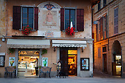 A couple buys gelato from a gelateria (gelato shop) while a shopkeeper closes for the night, Orta San Giulio, Piedmont, Italy. For editorial use only.