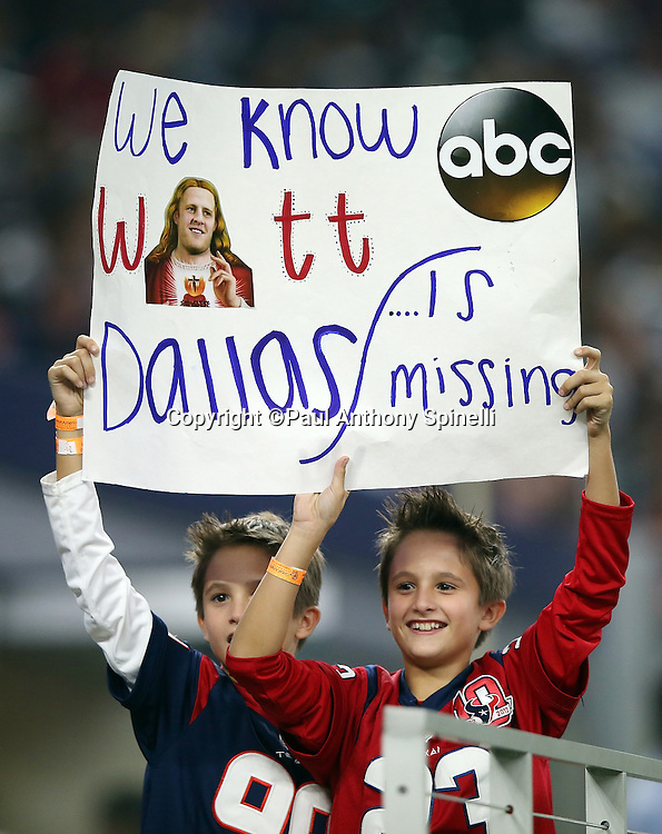 A pair of young Houston Texans fans wave a sign touting Houston Texans defensive end J.J. Watt (99) during the 2015 NFL preseason football game against the Dallas Cowboys on Thursday, Sept. 3, 2015 in Arlington, Texas. The Cowboys won the game 21-14. (©Paul Anthony Spinelli)