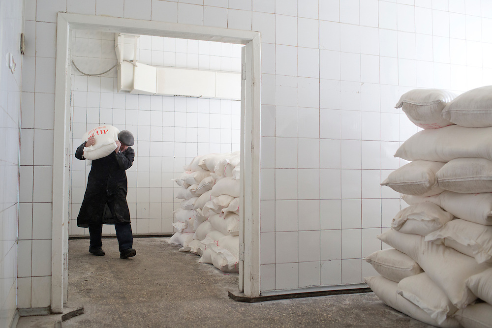 A mine worker carries a sack of sugar from a humanitarian aid convoy from Russia at Zasyadtko Mine on March 7, 2015 in Donetsk, Ukraine.