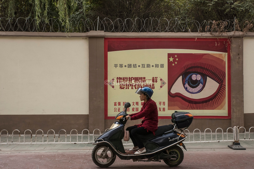 Kashgar. October 2nd, 2017<br /> Woman on a scooter driving along the walls of a reeducation camp decorated with a propaganda poster.