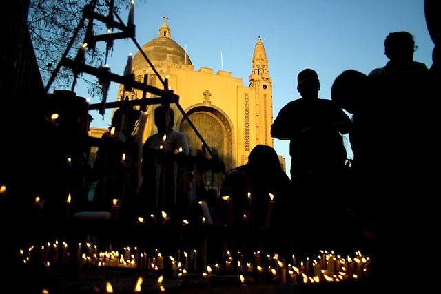 Faithfulls put candels during palm sunday at Lourdes church.