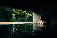 A young Asian woman in a spa pool at Santani Resort near the Knuckles Mountain Range, Kandy, Sri Lanka, Asia
