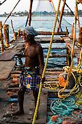 Een visserman bij oude chinese visnetten in Kochi