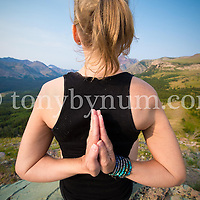 woman yoga pose on boulder big mountain background, glacier national park