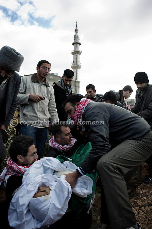 SYRIA - Al Qsair. Syrians men are seen as they are burying the body of Mohammad Baakour, 14 y.o. shot dead by a Syrian Army's sniper on  January 27, 2012. Al Qsair is a small town of 40000 inhabitants, located 25Km south-west of Homs. The town is besieged since the beginning of November and so far it counts 65 dead. ALESSIO ROMENZI