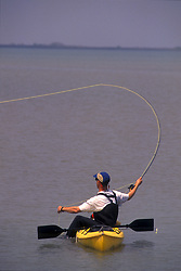 Stock photo of a man casting his fly fishing rod from his kayak