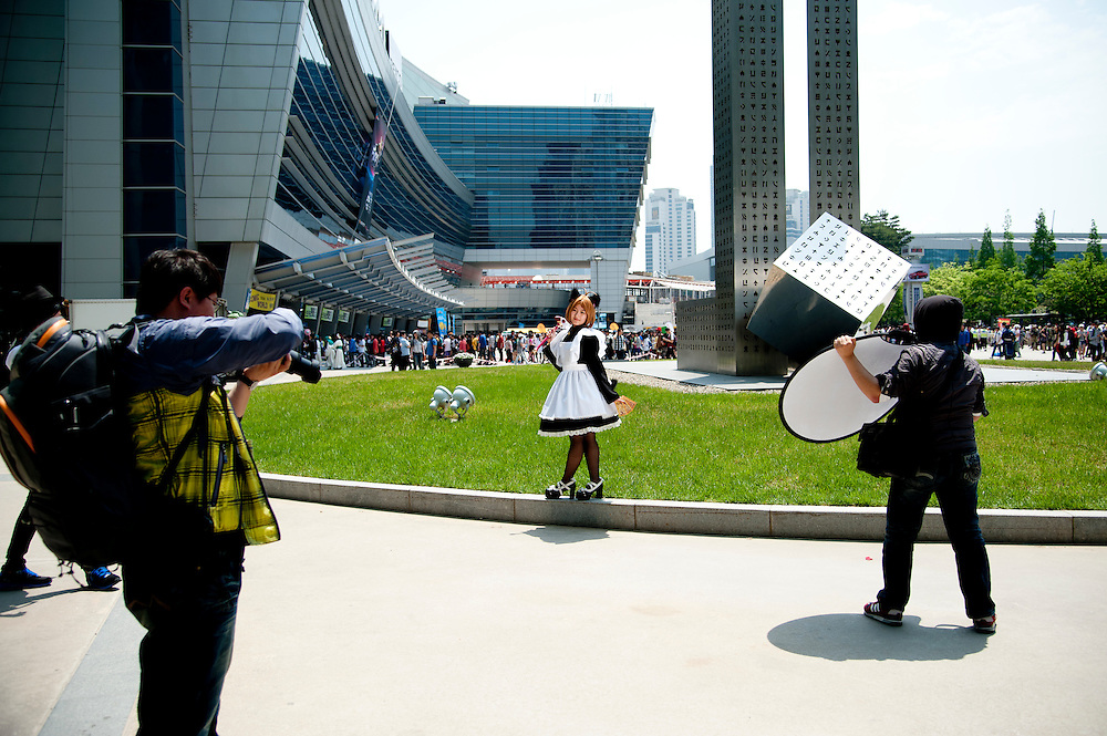 A girl dressed in character poses for photographers at Busan Comic World, a bi-monthly comic convention in Busan, South Korea, May 5, 2012.