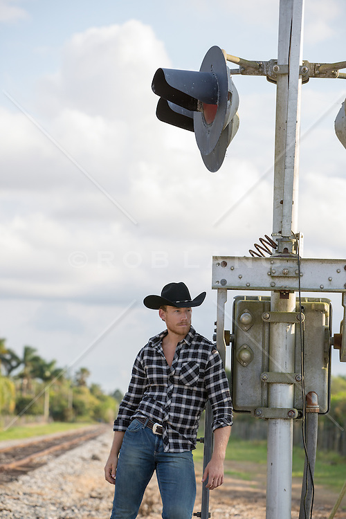 cowboy leaning against a railroad track signal