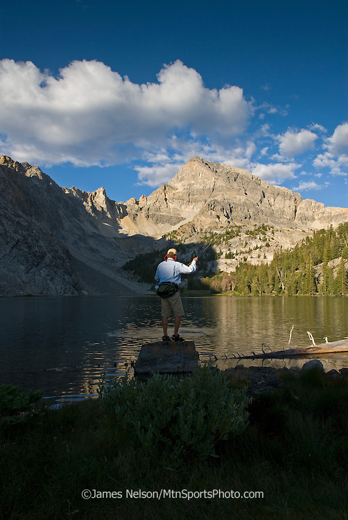 A angler plays a trout on an alpine lake in the Lost River Range of Idaho.
