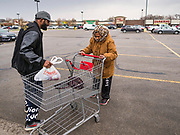 """11 APRIL 2020 - DES MOINES, IOWA: People pick up a ready to cook pasta meal at a food distribution in Des Moines. Most non-essential businesses in Iowa are closed until 30 April. Because of business closings causes by the Novel Coronavirus (SARS-CoV-2) pandemic, well over 100,000 Iowans filed first time claims for unemployment in the last three weeks, more than applied during the peak of the Great Recession of 2008. Local food banks have seen an unprecedented spike in people seeking nutritional assistance. Midwest Foods, a Des Moines based company and owner of Ginos Fine Italian Foods, gave away 1,000 complete dinners with sauce, noodles, salad, and dressing Saturday morning. People started lining up 3 hours before the food distribution began. The food distribution was done following """"social distancing"""" guidelines and all of the workers wore masks and gloves.     PHOTO BY JACK KURTZ"""