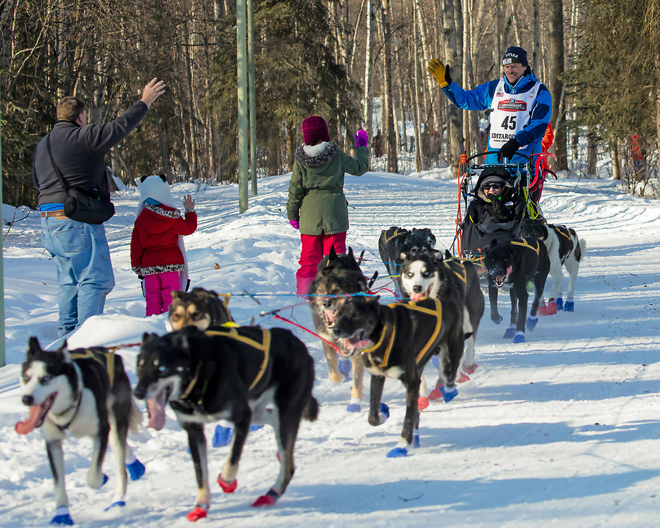Alaska. Musher Lars Monsen of Norway, greets spectators along the trails of Anchorage during the 2017 Iditarod Ceremonial start, Anchorage.