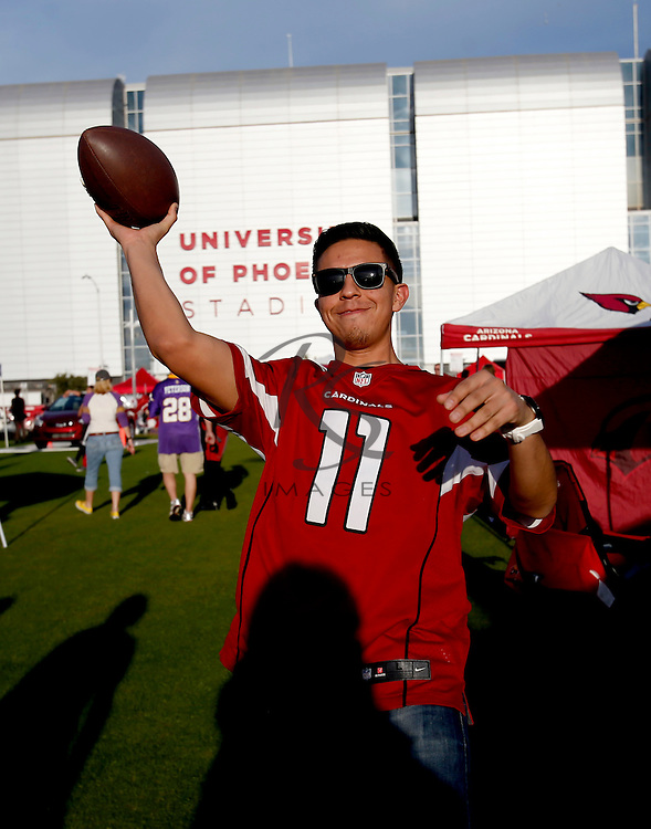 Theo Murillo catches a football prior to an NFL football game between the Minnesota Vikings and the Arizona Cardinals, Thursday, Dec. 10, 2015, in Glendale, Ariz. (AP Photo/Rick Scuteri)