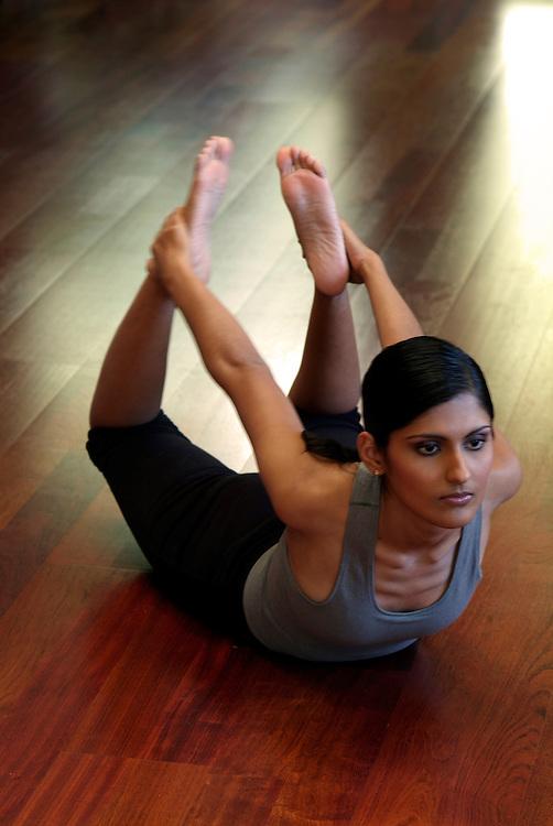 Wellness image of young woman doing yoga in studio