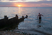 As the sun sets over fading daylight and calm waters of the Thames Estuary, a wild sea swimmer enters the water for his regular evening dip, on 18th July 2020, in Whitstable, Kent, England.