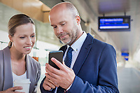 Portrait of businessman showing smartphone while talking to young attractive businesswoman in train station