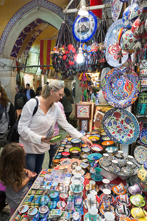 Western woman tourist buying hand-painted ceramics in The Grand Bazaar, Kapalicarsi, great market, Beyazi, Istanbul, Turkey