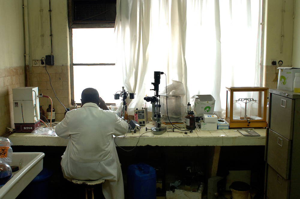 Kinshasa November 30, 2005 - Kinshasa General Hospital, Pharmaceutical researcher using a microscope-The Kinshasa General Hospital, is far from being a bush dispensary. With its 2,000 beds and its 2,250 employees (doctors, nurses and administrative personnel), it is one of Africa's most impressive medical facilities. It offers a full range of services and is the undisputed referral centre for the Congolese capital. Its patients the sick, accident victims and war casualties, both civilian and military  have one thing in common: their suffering, which the staff do their best to alleviate with the means available. But those means are often woefully inadequate