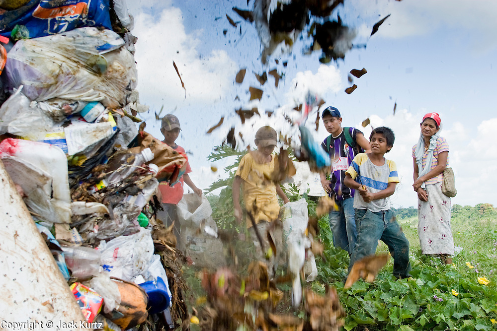 09 NOVEMBER 2004 - TAPACHULA, CHIAPAS, MEXICO: Carlos Lopez Perez, 12, center right, and other garbage pickers, wait for a garbage truck from Tapachula to unload in the municipal garbage dump in Tapachula, Chiapas, Mexico. About 130 people, the poorest of the poor in Tapachula, work in the dump picking through the garbage hoping to find tidbits they can use or sell to brokers who sit on the edge of the dump and resell the garbage. Most of the dump workers are Guatemalan migrants who crossed the border hoping, at one time, to get to the United States. Now they have settled for an existence on the very edge of Mexican society. PHOTO BY JACK KURTZ