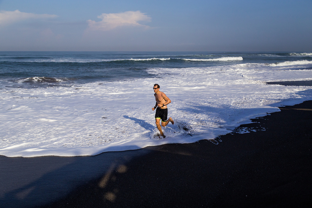 A man jogs on Batubelig beach, Canggu.