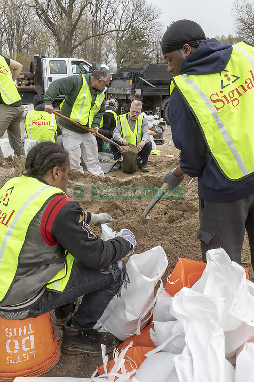May 2, 2019 - Detroit, Michigan, U.S. - Detroit, Michigan - Volunteers fill sandbags to protect homes along the Detroit River from expected floodiing due to high water levels in the Great Lakes. (Credit Image: © Jim West/ZUMA Wire)