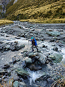 Tom rock hops across the Dart River during a day hike from Dart Hut to Cascade Saddle, in Mount Aspiring National Park, Otago region, South Island of New Zealand.