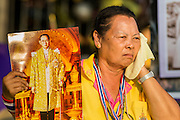 05 MAY 2104 - BANGKOK, THAILAND:  A Thai supporter of the monarchy with a photo of Bhumibol Adulyadej, the King of Thailand, wipes sweat from her face. Thousands of Thais packed the area around Sanam Luang and the Grand Palace Monday evening for a special ceremony to mark Coronation Day, which honored the 64th anniversary of the coronation of Bhumibol Adulyadej, the King of Thailand. Many of the people also support the anti-government movement led by Suthep Thaugsuban. Most of the anti-government protesters are conservative supporters of the monarchy.     PHOTO BY JACK KURTZ