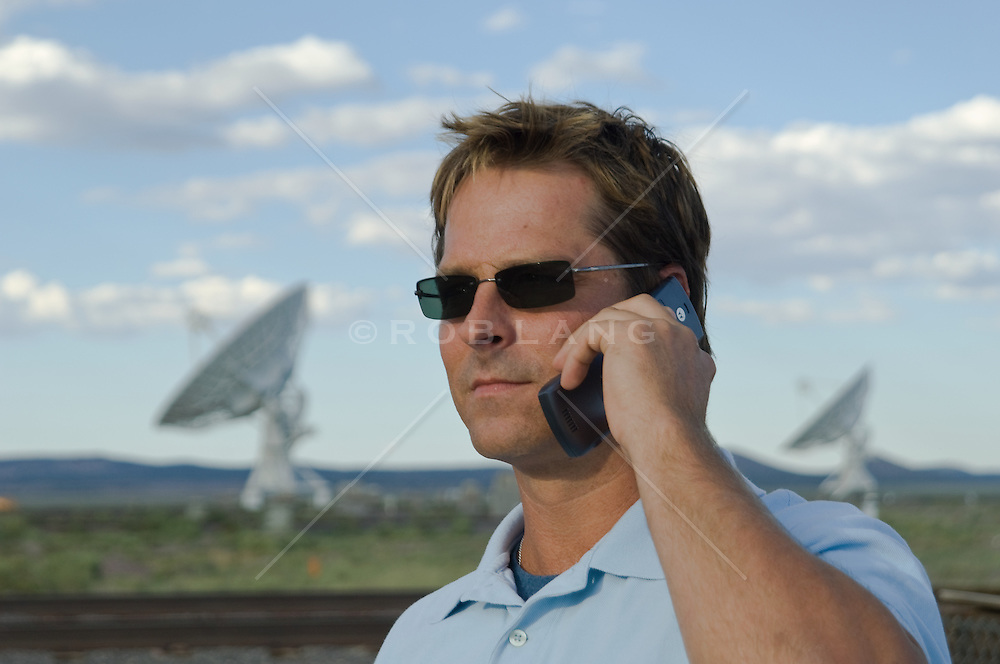 Man talking on his cell phone near a Very Large Array satellite dish in New Mexico