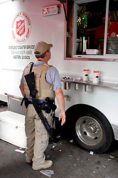 10th Sept, 2005. New Orleans, Louisiana, USA. .Hurricane Katrina. A member of the security services waits for hot food served from the Salvation Army truck parked on Canal Street..Photo; Charlie Varley