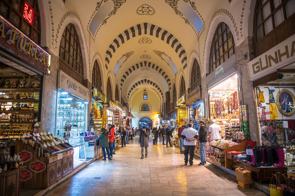 Looking down the main thoroughfare of the Istanbul Spice bazaar in Turkey with storefronts lining either side.