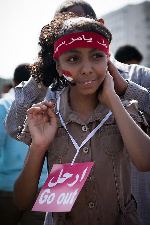 "During an anti-Morsi rally on Tahrir Square a girl carries a shield with the words ""Go out"" to demand the ouster of President Morsi. Cairo, Egypt, July 3, 2013"