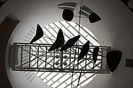 Looking up at a piece by Alexander Calder which is silhouetted by the dome architecture of Mario Batta.