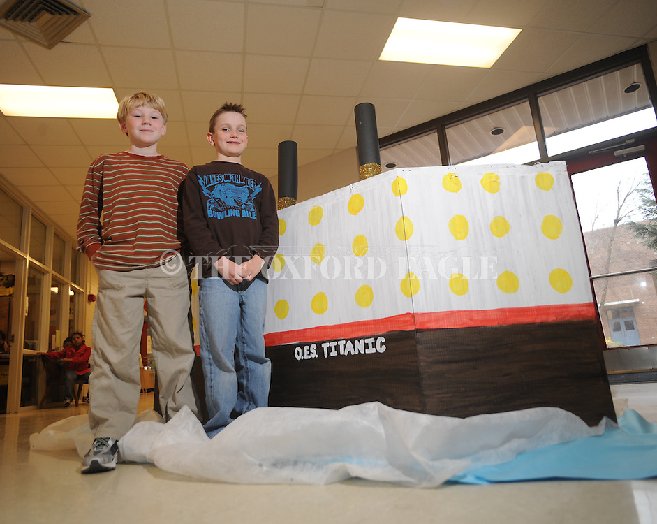 Oxford Elementary students Sam Barnard (left) and Luke Lilly both had ancestors on the Titanic. They pose with a boat students made in Oxford, Miss. on Monday, March 22, 2010.