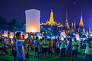 05 DECEMBER 2012 - BANGKOK, THAILAND:  With the spires of the Grand Palace in the background, people light lanterns that will float over Bangkok during the public ceremony to celebrate the birthday of Bhumibol Adulyadej, the King of Thailand, on Sanam Luang, a vast public space in front of the Grand Palace in Bangkok Wednesday night. The King celebrated his 85th birthday Wednesday and hundreds of thousands of Thais attended the day long celebration around the Grand Palace and the Royal Plaza, north of the Palace. The Thai monarch is revered by most Thais as unifying force in Thailand's society, which is not yet recovered from the political violence of 2010.     PHOTO BY JACK KURTZ