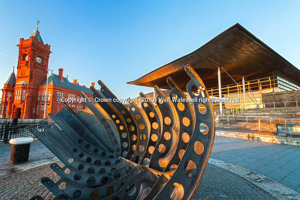 Senedd at sunset with lifeboat memorial in foreground<br /> Cardiff Bay<br /> Cardiff<br /> South<br /> Towns and Villages