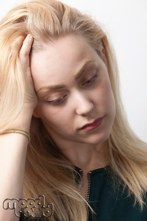 Young woman suffering from headache against white background
