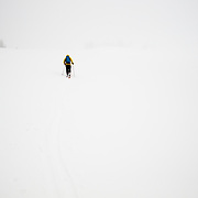 Forrest Jillson skins into the abyss to ski more untracked powder during a major winter storm in the Tetons.