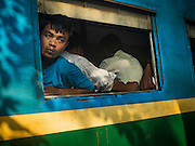 """25 OCTOBER 2015 - INSEIN, MYANMAR: Passengers on a train in the station next to Danyin Market (also known as Da Nyin) in Insein, Myanmar, about 90 minutes from Yangon. Vendors in the market sell just about everything people in the area need, but mostly it's a """"wet market"""" with fruits, vegetables and meats. Most people in Myanmar still do not have refrigerators in their homes, so people go to market almost every day.    PHOTO BY JACK KURTZ"""