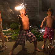 Friends enjoy fireworks sparklers during a summer night before the fourth of July.