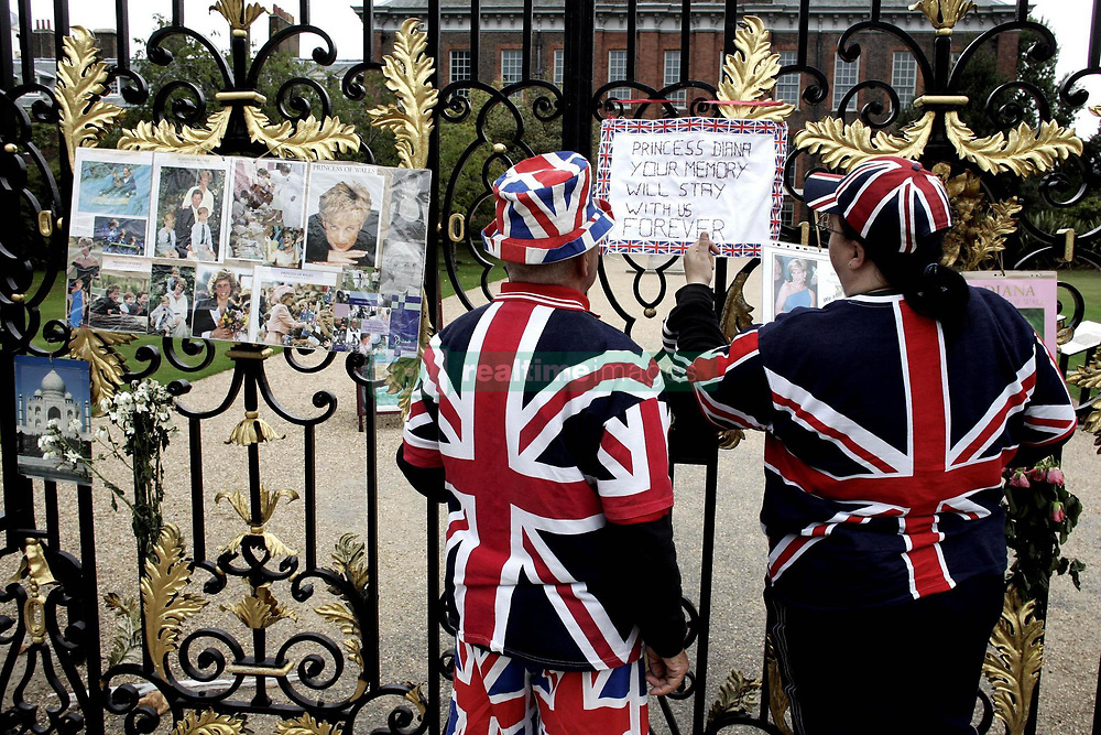 Terry Hutt (left) from Whaddon, Cambridgeshire, and Julie Cain from Newcastle read signs on the ninth anniversary of the death of Diana, Princess of Wales on the gates of her fomer London home, Kensington Palace.