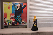 A traditionally-dressed woman walks past a poster for stylish arabic clothing in the modern city of Luxor, Nile Valley, Egypt.