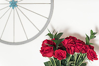 Simple yet elegant horizontal composition of fresh bouquet of red roses, set agains neutral cream colour wall with country style wall art.