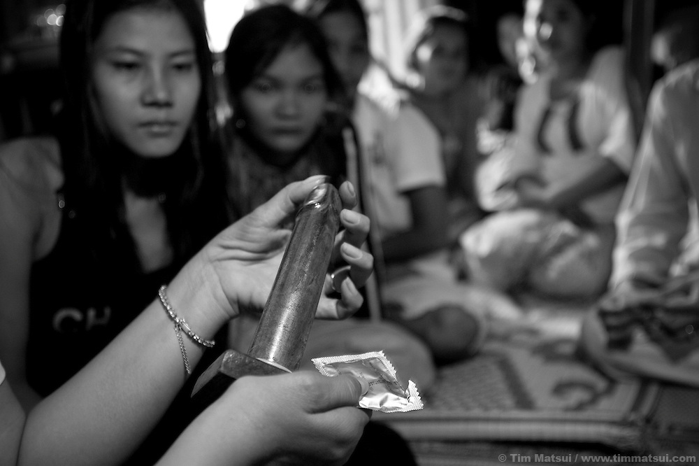 "Social worker team leader Ouch Vanna uses a wooden penis to demonstrate condom use to prostitutes in a slum where ""Acting for Women in Distressing Situations"" (AFESIP) conducts outreach and provides services in Phnom Penh, Cambodia. The slum's permanent structure, a decaying four story building known simply as 'The Building', was built in the 1960's as transitional housing and now hosts a shantytown where many of the city's poor live, including many prostitutes, and is believed to have the highest rate of HIV infection in the city. AFESIP hands out free condoms, instructs prostitutes on HIV prevention, and conducts outreach in case the prostitutes need medical services, choose to leave their profession, or can report on cases of sex trafficking. AFESIP offers housing, education, training, and counseling for women who are victims of sex trafficking, worked as prostitutes, or are escaping domestic violence. Founded by Somaly Mam, who herself was once a prostitute and victim of trafficking and domestic abuse, AFESIP has three facilities in Cambodia and works with other NGO's to provide long term care for the women."