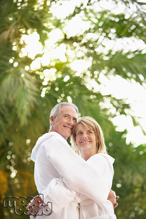 Middle-aged couple standing by palm trees hugging portrait