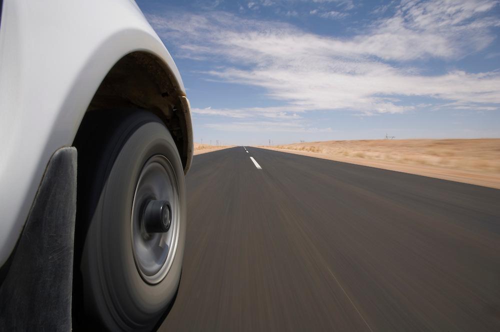 Africa, Namibia, Keetmanshoop, Low-angle view of safari truck driving on paved highway through Namib Desert