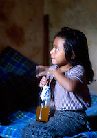 A young girl hits a soda bottle, Santiago Atitlan, Guatemala